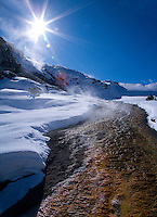 """A fine art landscape of a hot terrace stream descending through snow at Mammoth Hot Springs in Yellowstone National Park, Wyoming.  The brown rock exposed by the hot water creates a vibrant contrast with the surrounding white snow, brilliant blue sky, and sunburst radiating down.   This image pairs well with """"Mammoth Canary Spring No 1,"""" """"Sun Burst at Mammoth Main Terrace,"""" and """"Snow-swept Pine Near Hot Springs."""""""