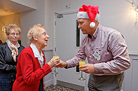 Pictured: One of the lottery millionaires gives a drink to a guast. Wednesday 28 November 2018<br /> Re: National Lottery millionaires from south Wales and the south west of England have hosted a glitzy Rat Pack-inspired Christmas party for an older people's music group at The Bear Hotel in Cowbridge, Wales, UK.