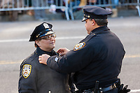 NEW YORK - NOVEMBER 24:  A NYPD Auxilliary Police officer gets an adjustment from a NYPD officer prior to the start the annual Macy's Thanksgiving Day Parade on Thursday, November 24, 2011.