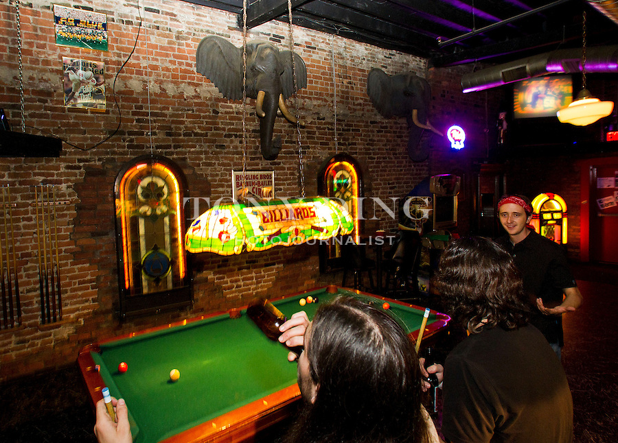 Ben Hogan, left, of Mt. Pleasant, Mich. take a break from a game of billiards with friends Dave Girdwood, and Ryan McPhee, in the Circus Bar of the Cavern Club, Saturday, Sept. 3, 2011 in Ann Arbor, Mich. (Tony Ding for The New York Times)