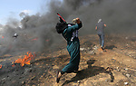 A Palestinian woman hurls stones towards Israeli security forces during clashes in tents protest where Palestinians demanding the right to return to their homeland, at the Israel-Gaza border, in Khan Younis in the southern Gaza Strip, on May 11, 2018. Photo by Ashraf Amra