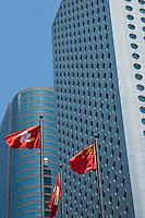Chinese flags flying in front of modern skyscrapers, Hong Kong Island, Hong Kong, China.
