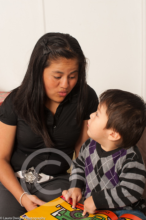 Two year old toddler boy with mother read to pointing at picture and talking (close to age 3)