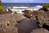 Tourists play in the warm ponds of Oheo Gulch, a popular spot off the Hana Highway on Maui.