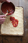 Chef using a wooden spoon to add tomato sauce to an unbaked square pizza with sliced mozzarella.