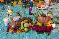 Matatlan, Oaxaca; Mexico; North America.  Day of the Dead Celebration.  Offerings in front of Family Altar.  Bread of the dead (pan de muertos), jicama, oranges, mezcal, alcohol, liquor, bananas, chocolate, incense. apple.