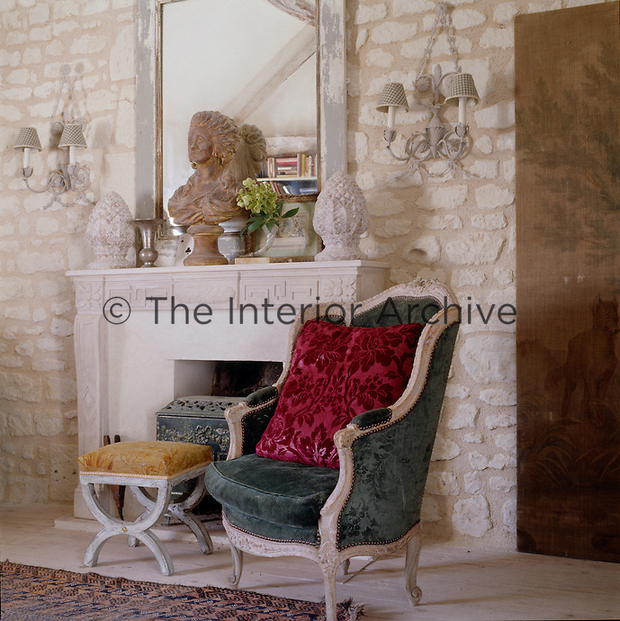 A Louis XVI high-back armchair and a footstool have been placed beside the fireplace in this sitting room