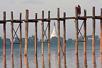 Myanmar, Burma, Mandalay, Amarapura.  Buddhist Monk on the U Bein Bridge at the end of the day.  The teak footbridge is 200 years old, and 1300 yards long.