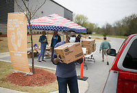 """Volunteer Kunle Babalola loads a box of Tyson chicken into the bed of a truck, Saturday, April 3, 2021 at Sam's Furniture in Springdale. Samaritan's Feet distributed approximately 720 pairs of shoes to pre-registered students from 18 elementary schools across Springdale in a """"drive-thru"""" event. Each recipient received a """"Hope Tote"""" drawstring book bag that contains a new pair of athletic shoes, socks, hygiene kit and a """"hope note"""" with an encouraging message submitted online from Samaritan's Feet supporters. Check out nwaonline.com/210404Daily/ for today's photo gallery. <br /> (NWA Democrat-Gazette/Charlie Kaijo)"""