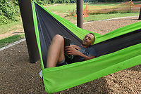 COOL MORNING HANGOUT<br />Carl Reed of Rogers enjoys cool morning temperatures on Wednesday July 21 2021 to relax and read at a hammock station along the Razorback Greenway in Rogers. The hammock hangout is at the Mercy Trailhead near Mercy Hospital. Another greenway hammock station is located at Lake Springdale. Go to nwaonline.com/210722Daily/ to see more photos.<br />(NWA Democrat-Gazette/Flip Putthoff)