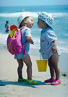 Two toddlers at the beach about to kiss.