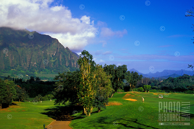 Fluted cliffs of the Koolau mountain range form the backdrop for golfers at the picturesque Koolau Golf Course on Oahu