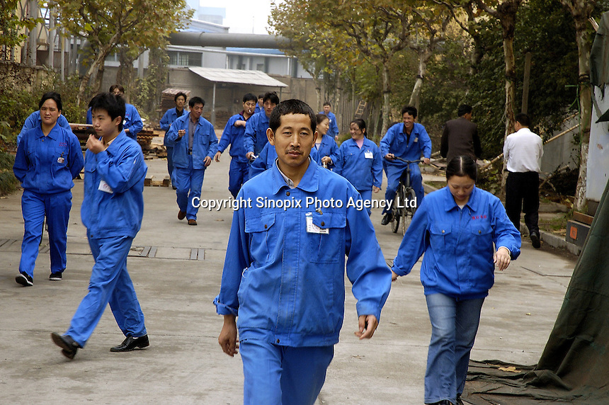 Workers leaving privately owned wood flooring factoryfactory at lunchbreak.