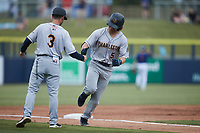 Brett Wisely (5) of the Charleston RiverDogs shakes hands with third base coach Blake Butera (3) after hitting a home run during the game against the Kannapolis Cannon Ballers at Atrium Health Ballpark on July 1, 2021 in Kannapolis, North Carolina. (Brian Westerholt/Four Seam Images)