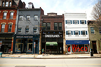 A woman walks past businesses along Butler Street on Friday March 20, 2020 in the Lawrenceville neighborhood of Pittsburgh, Pennsylvania. (Photo by Jared Wickerham/Pittsburgh City Paper)