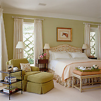 Arranged adjacent to the double bed is a comfortable armchair with a matching footstool upholstered in warm olive velvet with a reading light above