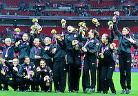 August 09, 2012: Christie Rampone, Kelley O'Hara and Abby Wambach jump with joy at the conclusion of award ceremony for women's Football  Final match at the Wembley Stadium on day thirteen in Wembley, England. USA defeat Japan 2-1 to win it's third consecutive Olympic gold medal in women's soccer. ..