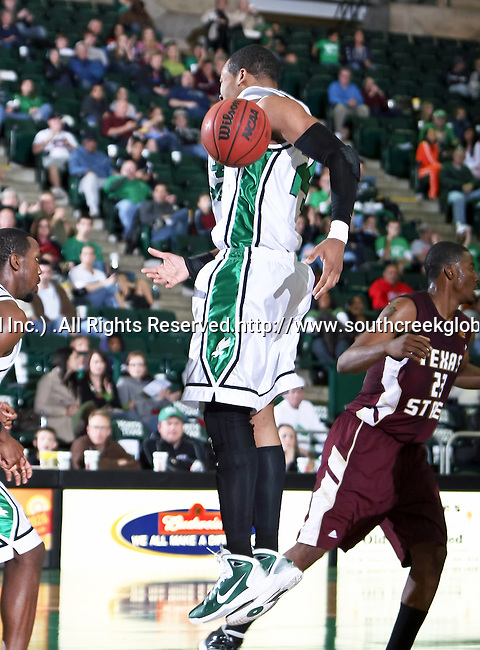 North Texas Mean Green forward Kedrick Hogans (24) misses a rebound in the game between the Texas State Bobcats and the University of North Texas Mean Green at the North Texas Coliseum,the Super Pit, in Denton, Texas. UNT defeated Texas State 85 to 62