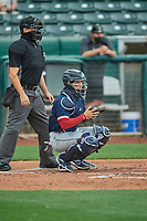 José Godoy (27) of the Tacoma Rainiers on defense against the Salt Lake Bees as home plate umpire Derek Eaton makes the calls at Smith's Ballpark on May 16, 2021 in Salt Lake City, Utah. The Bees defeated the Rainiers 8-7. (Stephen Smith/Four Seam Images)