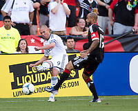 Kyle Porter (19) of D.C. United has the ball crossed past him by Kenny Miller (9) of the Vancouver Whitecaps during a Major League Soccer match at RFK Stadium in Washington, DC. D.C. United lost to the Vancouver Whitecaps, 1-0.