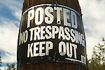 No trespassing sign nailed to a wooden pole