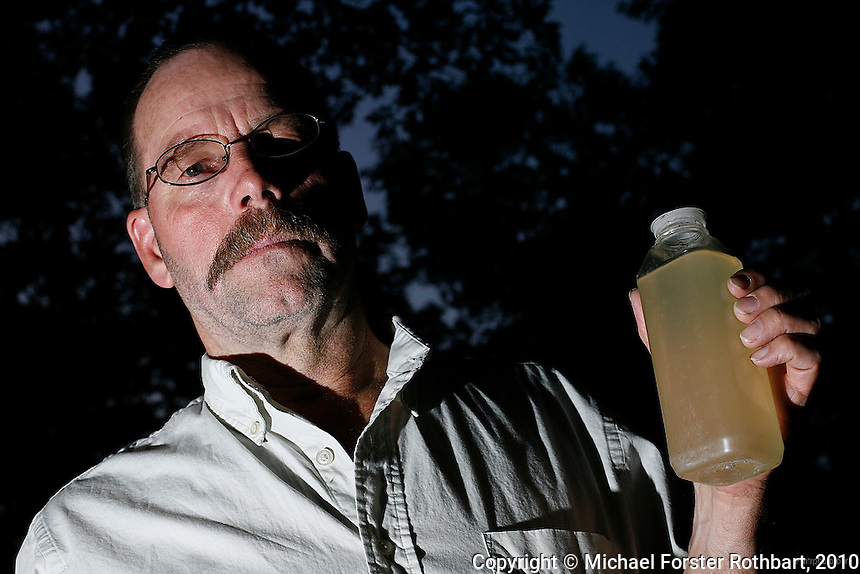 """Craig Sautner of Dimock, PA, holds a bottle of his contaminated tap water collected in March 2010. Their water problems started in September 2008 after natural gas drilling on their property a month earlier. """"Our water smells of diesel fuel,"""" says Sautner. """"In our water, we've found aluminum, manganese, chloride, iron, magnesium, sodium, strontium-T, all above the EPA limits, and TDS [Total Dissolved Solids] and other elements we can't disclose yet."""" <br /> <br /> Craig and Julie Sautner are among 14 families along Carter Road whose drinking water wells became contaminated with methane and other chemicals. Cabot Oil and Gas, the company held responsible by the Pennsylvania Department of Environmental Protection, has had at least 21 spills in Dimock Township in less than two years. The Sautners' well has so much methane that Craig can sometimes light his water on fire, and Cabot had to install an exhaust pipe to vent off excess methane.<br /> <br /> Hydraulic fracturing or """"fracking"""" is new method of drilling for natural gas: millions of gallons of water, sand and proprietary chemicals are pumped down a well under high pressure. The pressure fractures the shale, opening fissures so that natural gas can flow more freely. In August 2010, fracking is being widely used in the Marcellus Shale formation under Pennsylvania while New York considers a moratorium until the environmental effects can be reviewed. <br /> <br /> The 2005 Energy Policy Act exempted natural gas drilling from the Safe Drinking Water Act. Scientists have identified volatile organic compounds (VOCs) such as benzene, ethylbenzene, toluene, methane and xylene that have been found in contaminated drinking water near drilling sites.<br /> <br /> © Michael Forster Rothbart<br /> www.mfrphoto.com <br /> 607-267-4893 o 607-432-5984<br /> 5 Draper St, Oneonta, NY 13820<br /> 86 Three Mile Pond Rd, Vassalboro, ME 04989<br /> info@mfrphoto.com<br /> Photo by: Michael Forster Rothbart<br /> Date: 8/2010    File#:"""