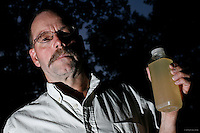 "Craig Sautner of Dimock, PA, holds a bottle of his contaminated tap water collected in March 2010. Their water problems started in September 2008 after natural gas drilling on their property a month earlier. ""Our water smells of diesel fuel,"" says Sautner. ""In our water, we've found aluminum, manganese, chloride, iron, magnesium, sodium, strontium-T, all above the EPA limits, and TDS [Total Dissolved Solids] and other elements we can't disclose yet."" <br /> <br /> Craig and Julie Sautner are among 14 families along Carter Road whose drinking water wells became contaminated with methane and other chemicals. Cabot Oil and Gas, the company held responsible by the Pennsylvania Department of Environmental Protection, has had at least 21 spills in Dimock Township in less than two years. The Sautners' well has so much methane that Craig can sometimes light his water on fire, and Cabot had to install an exhaust pipe to vent off excess methane.<br /> <br /> Hydraulic fracturing or ""fracking"" is new method of drilling for natural gas: millions of gallons of water, sand and proprietary chemicals are pumped down a well under high pressure. The pressure fractures the shale, opening fissures so that natural gas can flow more freely. In August 2010, fracking is being widely used in the Marcellus Shale formation under Pennsylvania while New York considers a moratorium until the environmental effects can be reviewed. <br /> <br /> The 2005 Energy Policy Act exempted natural gas drilling from the Safe Drinking Water Act. Scientists have identified volatile organic compounds (VOCs) such as benzene, ethylbenzene, toluene, methane and xylene that have been found in contaminated drinking water near drilling sites.<br /> <br /> © Michael Forster Rothbart<br /> www.mfrphoto.com <br /> 607-267-4893 o 607-432-5984<br /> 5 Draper St, Oneonta, NY 13820<br /> 86 Three Mile Pond Rd, Vassalboro, ME 04989<br /> info@mfrphoto.com<br /> Photo by: Michael Forster Rothbart<br /> Date: 8/2010    File#:  Canon 5D digital camera frame 68410"