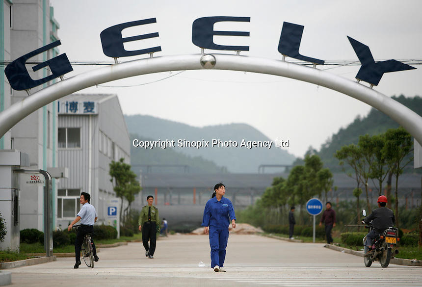 Workers at the Geely Automobile's factory walk past the entrance of the company's factory complex in Taizhou, Zhejiang Province, China..