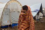 DOMIZ, IRAQ: A Syrian refugee pulls his sweater up to keep warm in the Domiz refugee camp in the Kurdish region of northern Iraq...The semi-autonomous region of Iraqi Kurdistan has accepted around 60,000 refugees from war-torn Syria. Around 20,000 refugees live in the Domiz camp which sits 60 km from the Iraq-Syria border...Photo by Younes Mohammad/Metrography