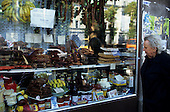 Belgrade, Serbia. Elderly woman looking at goods displayed in a shop window - sausages, bananas, cheese.