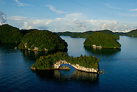 Aerial view of the Rock Islands in the late afternoon with the Natural Arch in the foreground Palau, <br /> Micronesia
