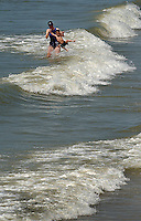 A mother helps her son jump the waves at Folly Beach, near Charleston, SC.