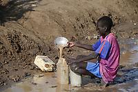KENYA, Turkana, refugee camp Kakuma IV, south sudanese boy fetch water after rain / KENIA, Turkana, Fluechtlingslager Kakuma 4, suedsudanesischer Junge schoepft Wasser nach einem Regen