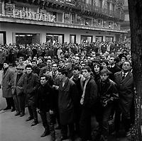 """Edifice commercial et de bureaux, magasin """"Au gaspillage"""" au début du XXe siècle, """"Au bon marché de Paris, """"le Printemps"""" et les assurances """"Le continent"""" dans les années 1960, """"Bouchara"""", """"Zara"""", 47 rue d'Alsace-Lorraine. 11 Mars 1964. Vue de la foule des badauds regroupés dans la rue Alsace-Lorraine, devant Printafix, suite à l'incendie de l'ilmmeuble du Printemps."""