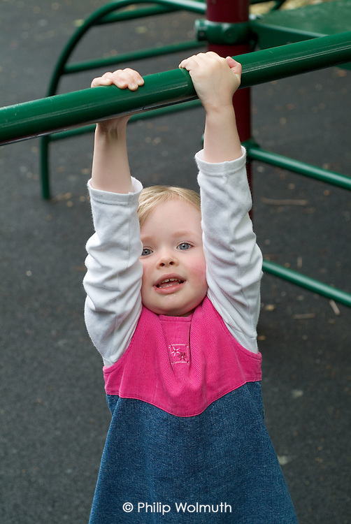 A young girl swings on play equipment in the under-5 area at Westminster City Council's Queens Park Gardens, London.