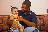 MR / Schenectady, NY. Infant (girl, 10 months, African American & Caucasian) laughs while being tickled by her father (22, African American). MR: Dal7, Dal4. ID: AL-HD. © Ellen B. Senisi