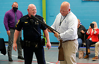Retiring city of Rogers police chief Hayes Minor (from right) receives an engraved Beretta Over and Under 12 gauge shotgun from David Crawford, president of the Rogers Fraternal Order of Police, and detective Rick Yager Wednesday, April 28, 2021, during a retirement reception in his honor at the Rogers Activity Center. Hayes served 27 years in law enforcement with the city and the last six as the police chief for the department. Check out nwaonline.com/210429Daily/ and nwadg.com/photos for a photo gallery.<br /> (NWA Democrat-Gazette/David Gottschalk)