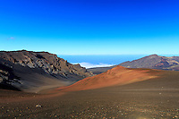 A wide-angle view of Maui's Haleakala Crater from the Sliding Sands Trail reveals a deep contrast between red dirt and blue sky.