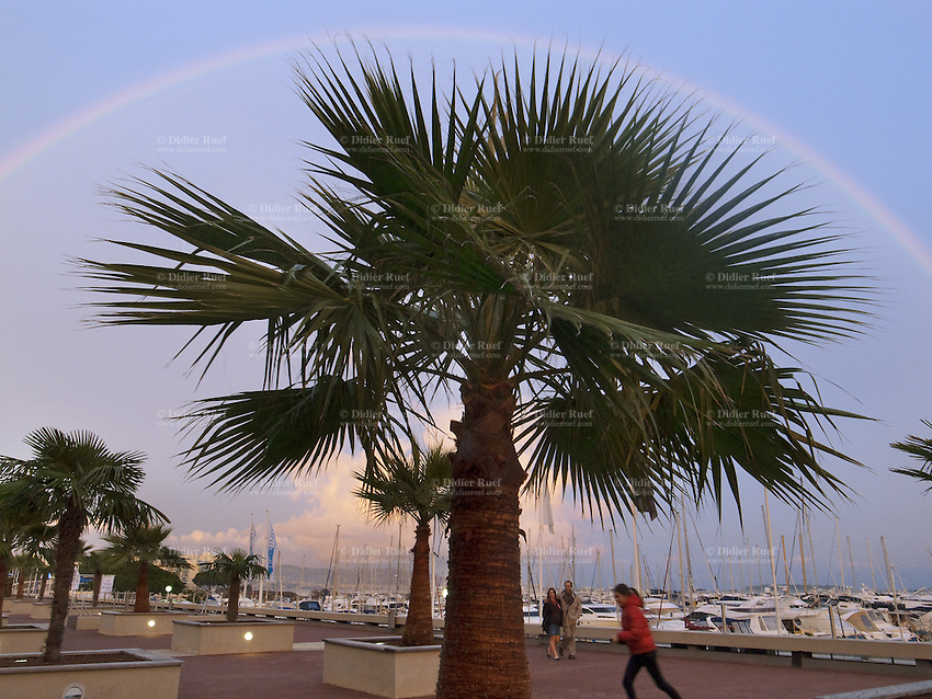 France. Alpes-Maritimes department. Mandelieu. Rainbow in the sky and palm trees. A couple is walking while a young teenager girl is running on the concrete asphalt. Mandelieu is distant 10 km from Cannes. 02.11.11  © 2010 Didier Ruef