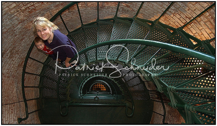 A mother and son pause to look up while walking down the many flights of stairs inside of the Currituck Lighthouse in Corolla, N.C. Photo is model released.