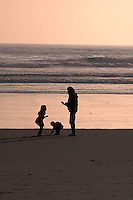 Silhouetted family at beach<br />