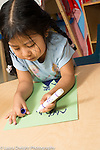 Education Preschool 4 year olds girl writing letters with marker using left hand