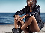 Young woman in black leather jacket sitting at the beach Image © MaximImages, License at https://www.maximimages.com