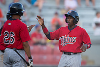 Manuel Guzman (7) of the Elizabethton Twins high fives a teammate after scoring a run against the Kingsport Mets at Hunter Wright Stadium on July 9, 2015 in Kingsport, Tennessee.  The Twins defeated the Mets 9-7 in 11 innings. (Brian Westerholt/Four Seam Images)