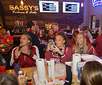 NWA Democrat-Gazette/JASON IVESTER<br /> Arkansas soccer players Lindsey Mayo (from left), Cameron Carter and Ellie Breden celebrate while watching the selection show on Monday, Nov. 7, 2016, at Sassy's Barbeque & Grille in Fayetteville. The Razorbacks will host Memphis on Friday in the first round of the NCAA tournament.