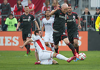Toronto, Ontario - May 3, 2014: Toronto FC midfielder Michael Bradley #4 and New England Revolution midfielder Andy Dorman #12 in action during a game between the New England Revolution and Toronto FC at BMO Field.