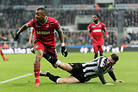 (L-R) Jordan Ayew of Swansea City challenged by Ciaran Clark of Newcastle during the Premier League match between Newcastle United and Swansea City at St James' Park, Newcastle, England, UK. Saturday 13 January 2018