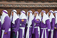 Antigua, Guatemala.  Cucuruchos Carrying Float (Anda) in a Religious Procession during Holy Week, La Semana Santa.