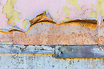 Peeling stucco on aging wall of building set for demolition show scars of time.