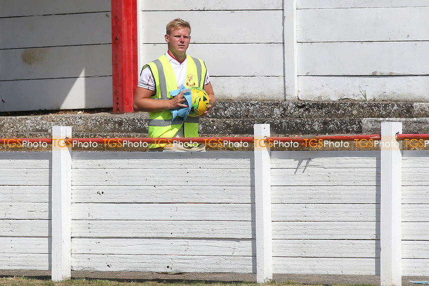 A steward disinfects the ball prior to throwing it back into play during Ramsgate vs Folkestone Invicta, Friendly Match Football at Southwood Stadium on 1st August 2020